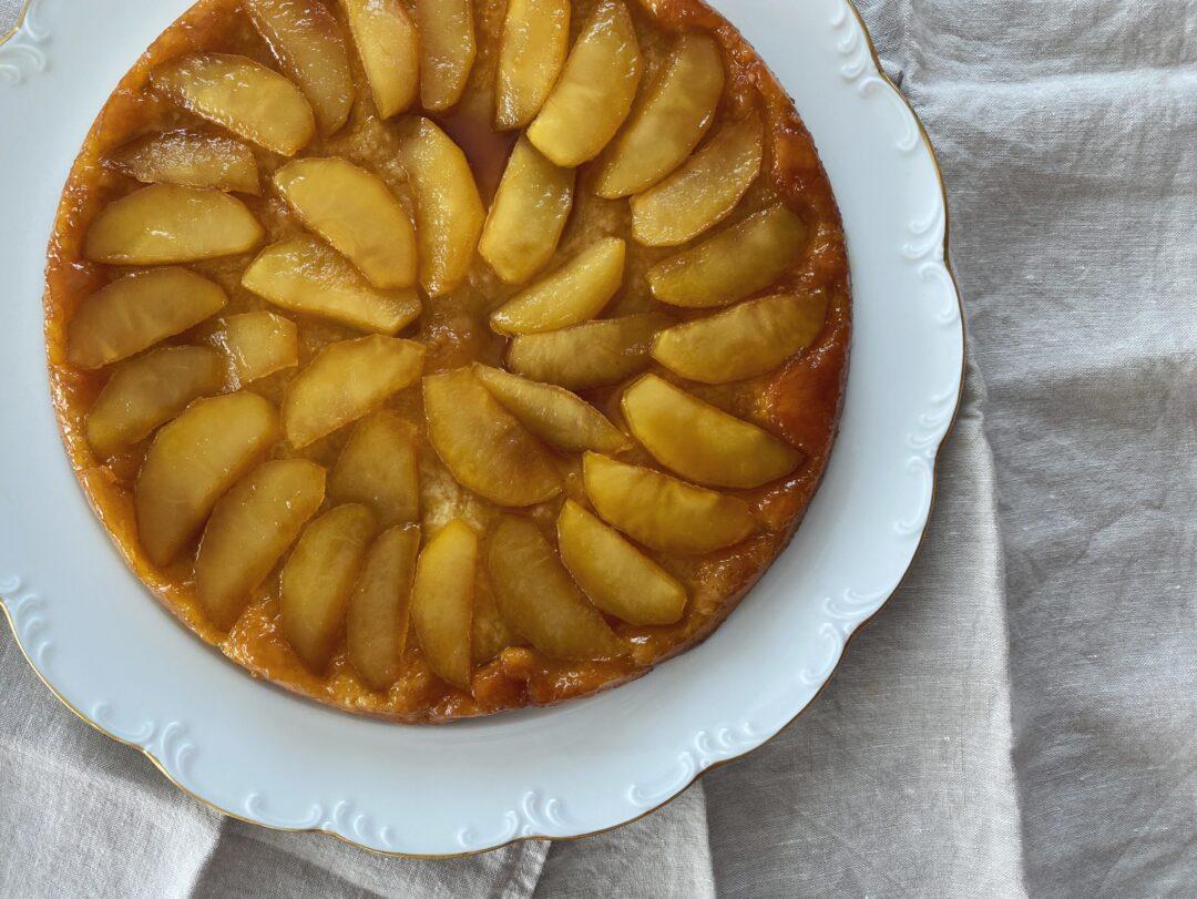 Tarte Tatin - französischer Apfelkuchen auf einem weissen Teller mit Goldrand, platziert auf beigen Leinenservietten