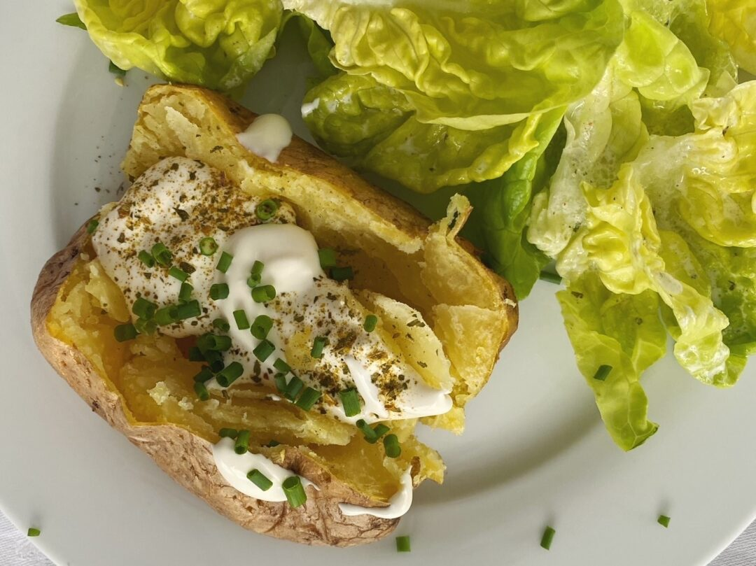 Ofenkartoffeln mit Sauerrahm und Kräutern, neben einem grünen Salat