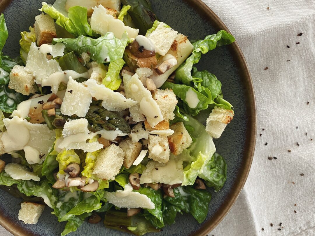 Caesars Salad mit Spargeln, gebratenen Pilzen, Brotwürfeln und hausgemachtem Dressing in einer blau-braunen Schüssel angerichtet.
