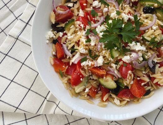 Griechischer Salat in weisser Schüssel, auf weissem Tischtuch mit schwarzem Karo-Muster