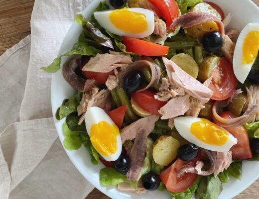 Salade Niçoise mit Sardellen, Thon, Eiern und Oliven in einer weissen Schüssel serviert