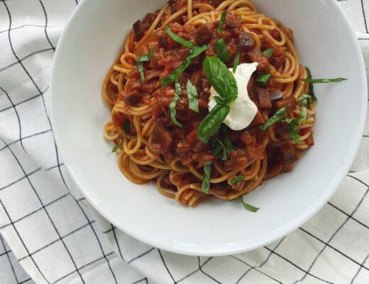 Pasta alla Norma mit Auberginen und Tomaten in einer weissen Schüssel serviert, die auf einem schwarz karierten Tischtuch steht
