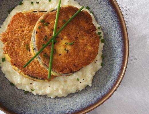 Auberginen-Piccata auf Weisswein-Risotto angerichtet auf einem blauen Teller mit braunem Rand